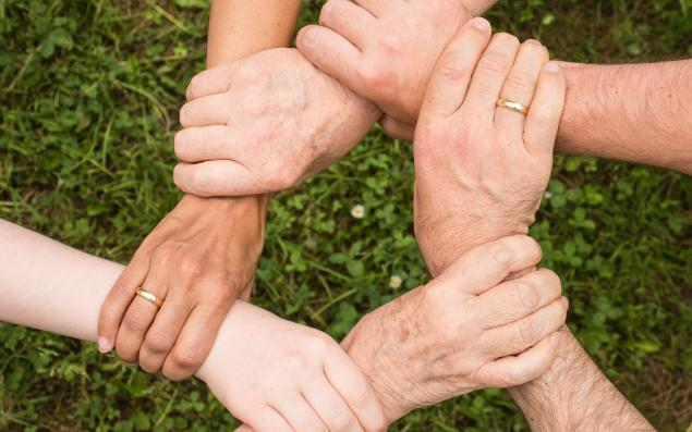 Photo of people holding arms