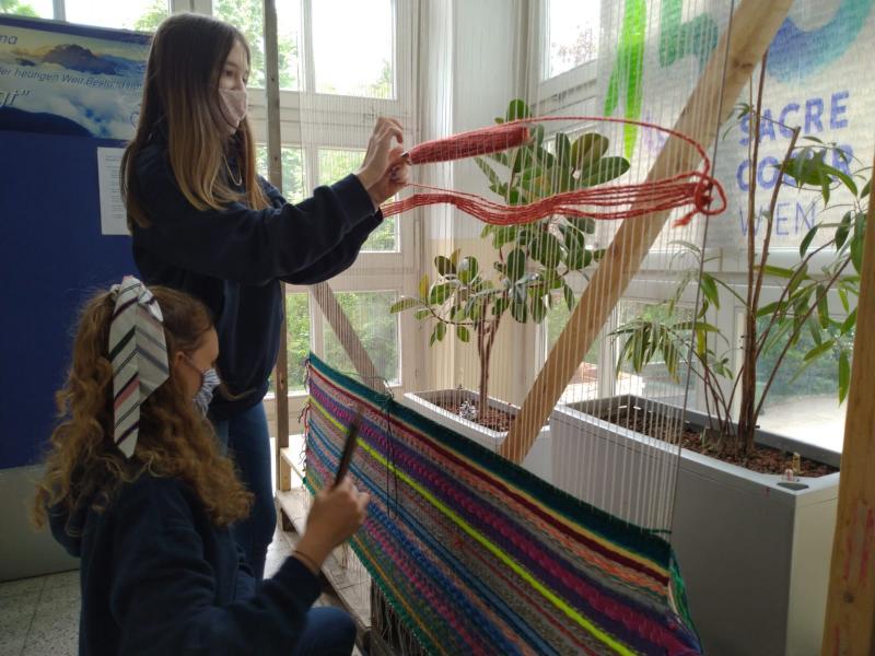 Estudiantes tejiendo con hilos multicolores