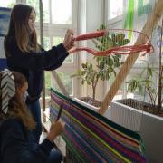 Des élèves tissant des tapisseries aux fils multicolores